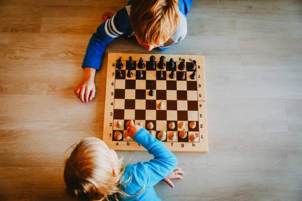 kleine jungen und mädchen spielen schach - kindergarten workshop stock-fotos und bilder
