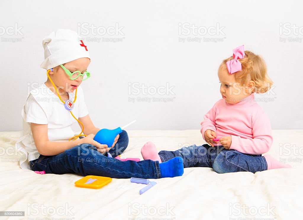 little boy and girl play doctor indoors stock photo