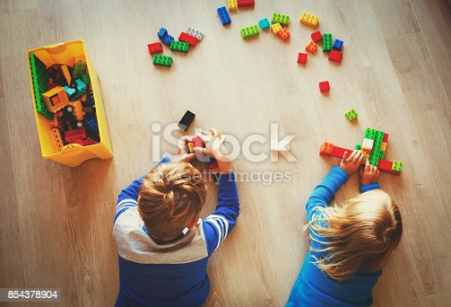 istock little boy and girl play with plastic blocks 854378904