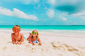 little boy and girl play with sand on tropical beach