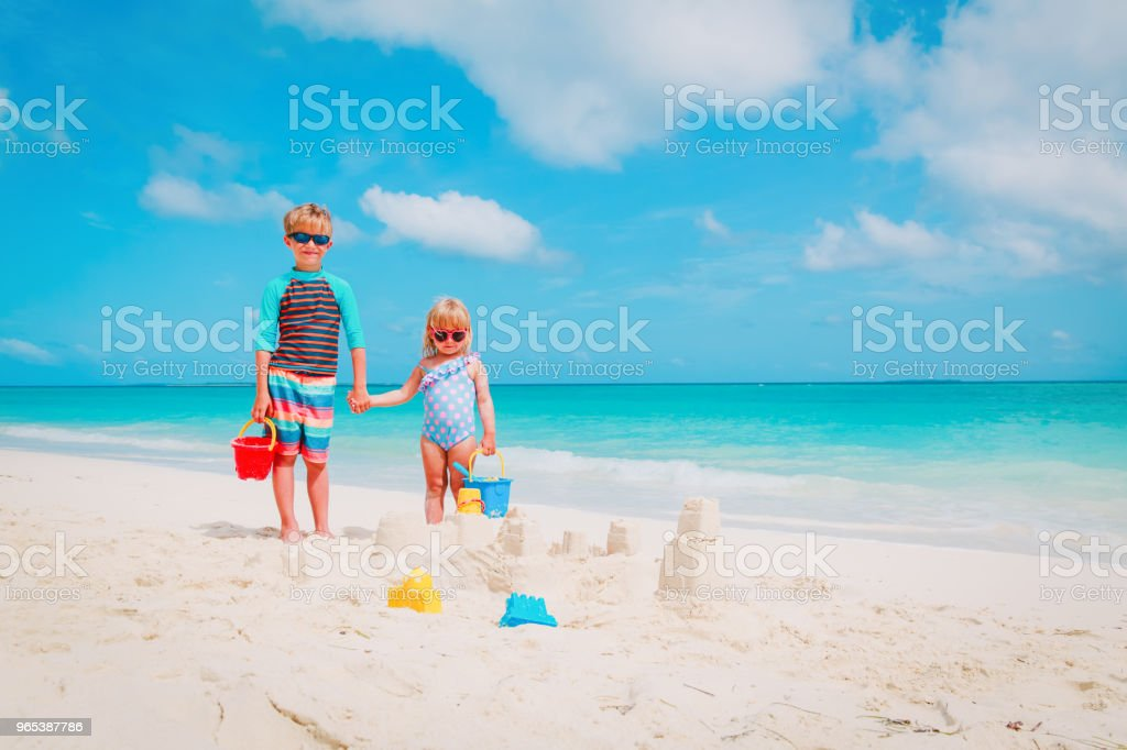 little boy and girl play with sand on beach royalty-free stock photo