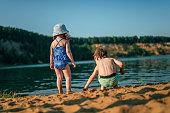 Brother and sister enjoying nature near lake