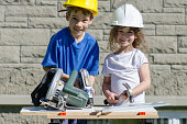 Caucasian boy drilling while his sister is holding a hammer, on the workbench. The boy wears a yellow hard hat and the girl a white hard hat. They are outside in the backyard during a day of summer.