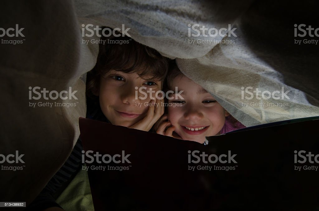 Little boy and girl reading under bed sheets before sleep stock photo