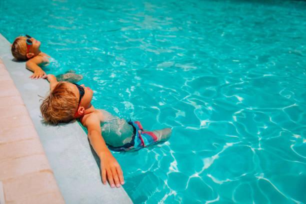 Kleine Junge und Mädchen entspannen sich im Pool, Familie auf Badeort – Foto