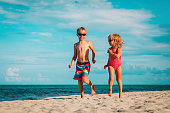 happy little boy and girl run play at beach vacation