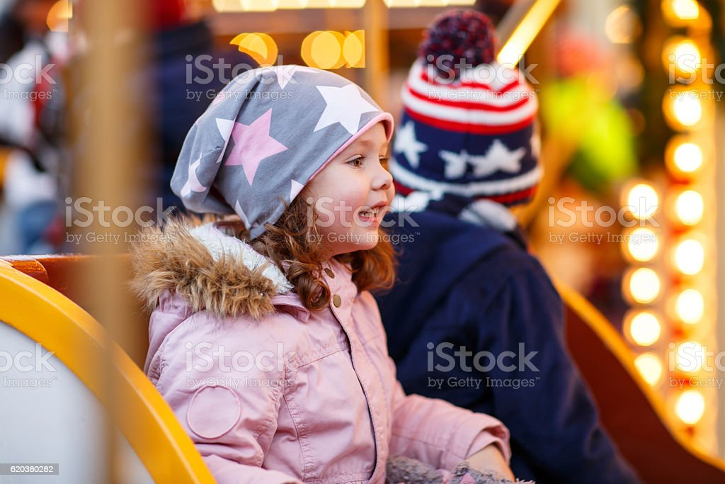 little boy and girl, siblings on carousel at Christmas market zbiór zdjęć royalty-free