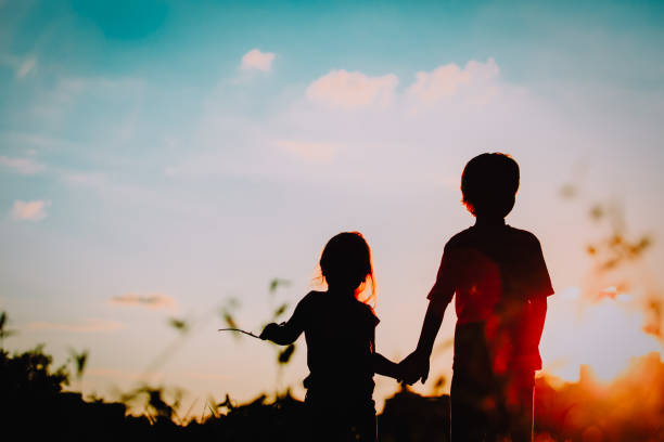 little boy and girl silhouettes holding hands at sunset stock photo