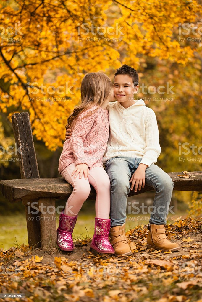 Little Boy And Girl Sitting In Autumn Park Little boy and girl, brother and sister are sitting on wooden bench in the autumn park. Girl is kissing her brother. Autumn Stock Photo
