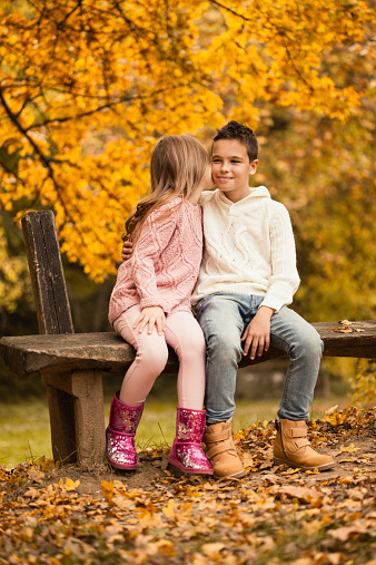Little Boy And Girl Sitting In Autumn Park Stock Photo - Download Image Now