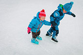 little boy and girl skating together in winter snow, kids winter sport