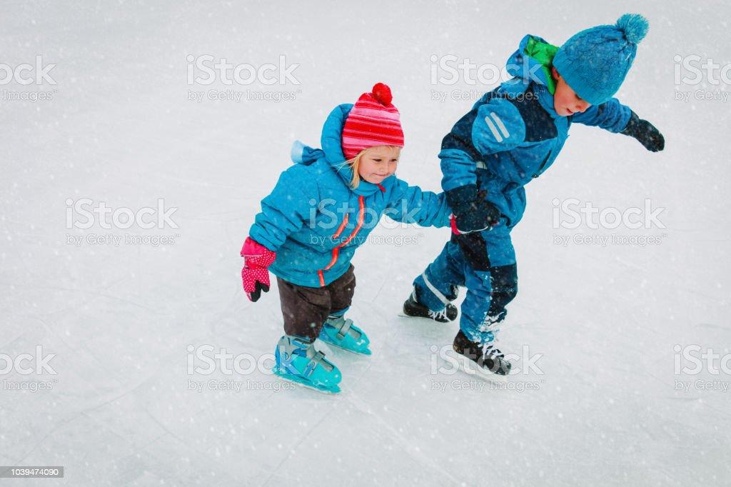小さな男の子と女の子一緒にアイススケート、子供の冬のスポーツ ストックフォト