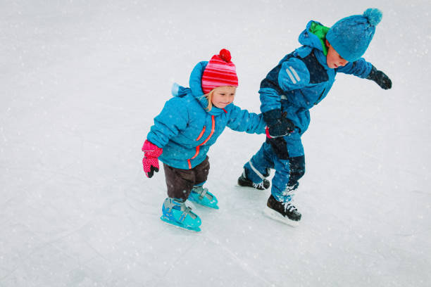 little boy and girl skating together, kids winter sport little boy and girl skating together in winter snow, kids winter sport ice skating stock pictures, royalty-free photos & images