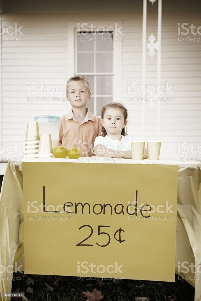 Little Boy and Girl Standing Behind Old Fashioned Lemonade Stand royalty-free stock photo