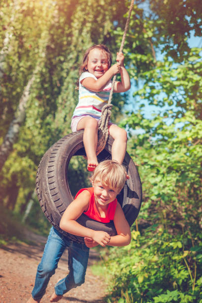 Little boy and girl swinging in summer stock photo