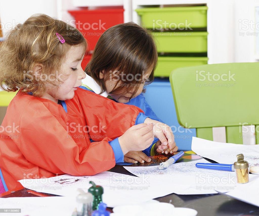 Little Boy And Girl Using Glitter stock photo