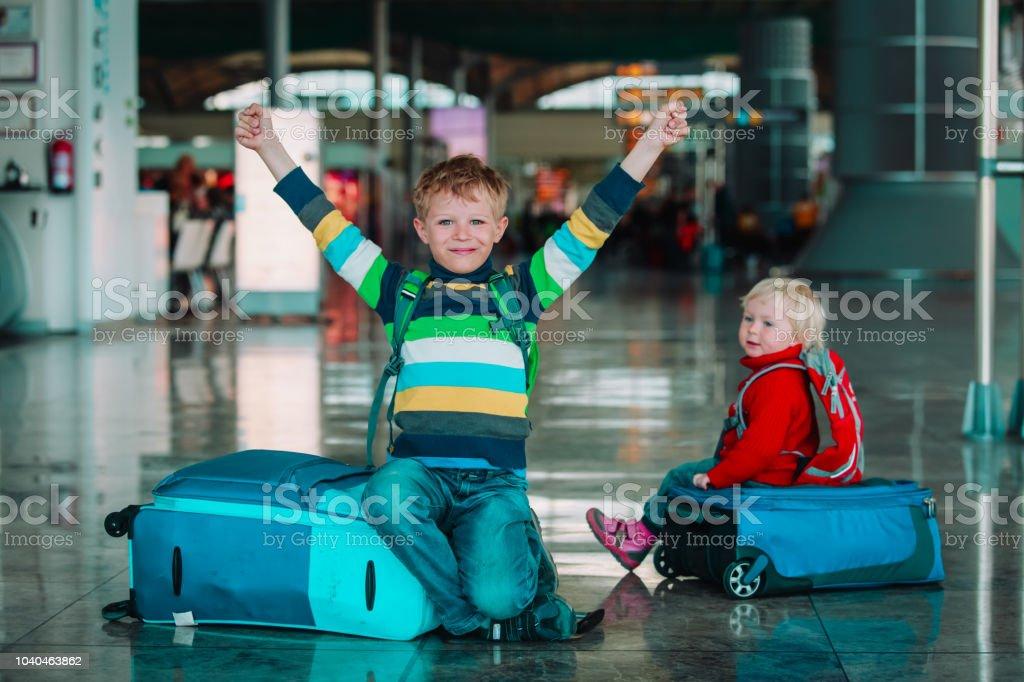 男の子と女の子、家族旅行の空港で待つ ストックフォト