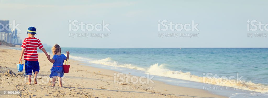 little boy and girl walking on beach stock photo