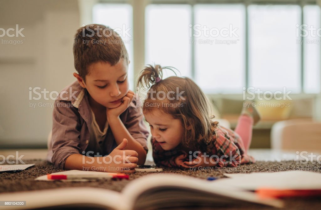Little boy and girl watching cartoons on mobile phone while relaxing on the carpet. stock photo