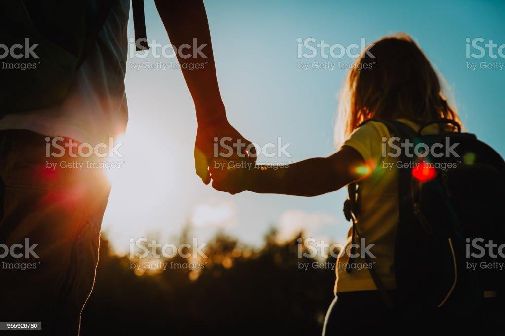 男の子とサンセットで手を繋いでいるバックパックと女の子 ストックフォト