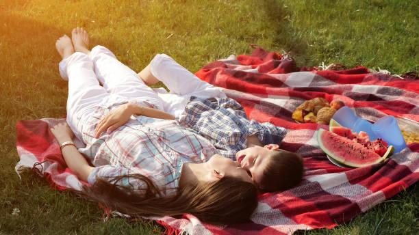 kleiner junge und glückliche mutter liegen und umarmen auf rote decke - jubeln mutter shirts stock-fotos und bilder