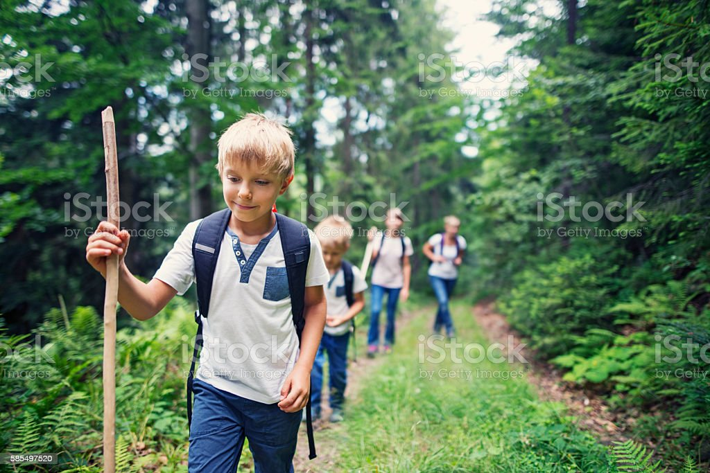 Little boy and his family hiking in forest stock photo