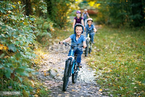 Little boy and his family riding bicycles in nature. The boy is smiling happily. Nikon D810