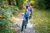 Little boy and his family riding bicycles in nature. The boy is smiling happily.\nNikon D810