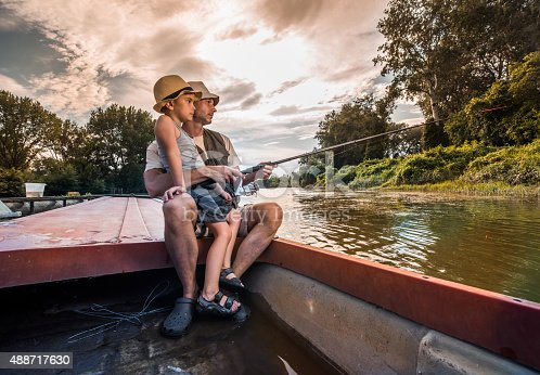 992209122 istock photo Little boy and his father freshwater fishing from a boat. 488717630