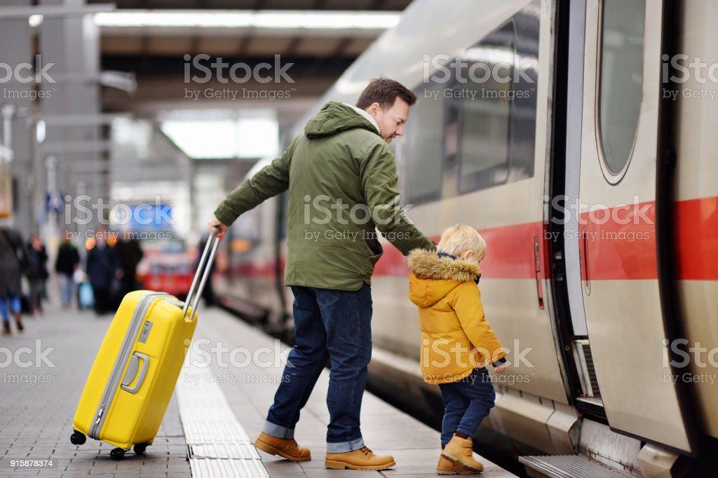 Niño y su padre ir en tren expreso de plataforma de la estación de ferrocarril - foto de stock