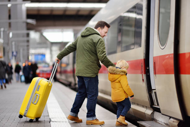 little boy and his father go in express train on railway station platform - getting on stock photos and pictures