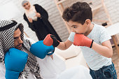 A little boy and his father in Arabian clothes train in boxing gloves. They are in a bright room with a bookcase. Nearby is the boy's mother in the hijab.