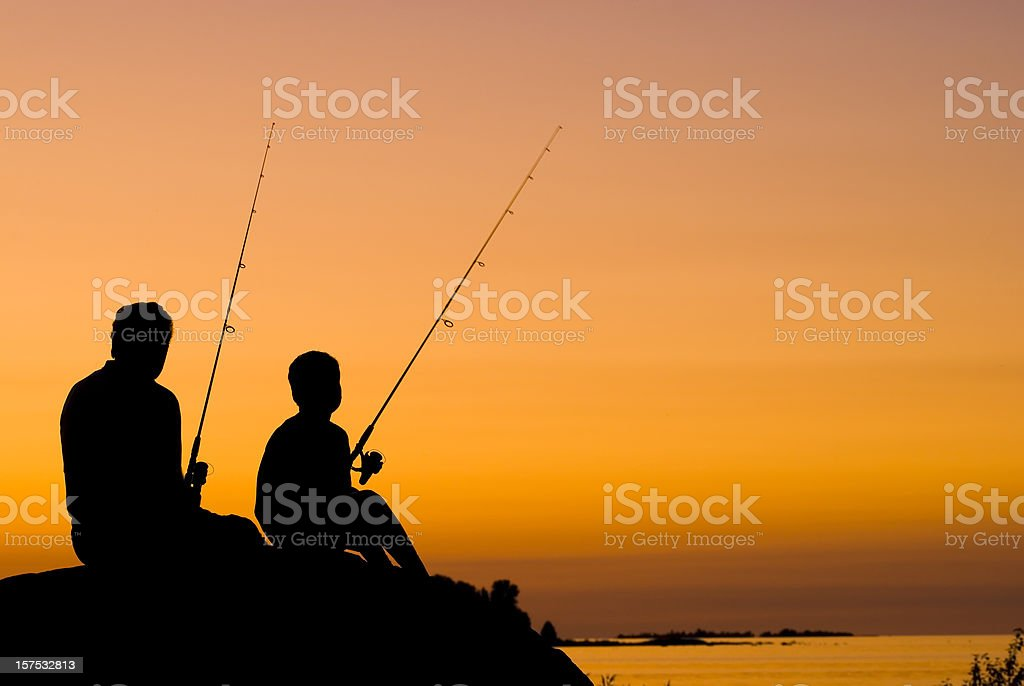 Little Boy And His Grandfather Fishing At Sunset - III stock photo