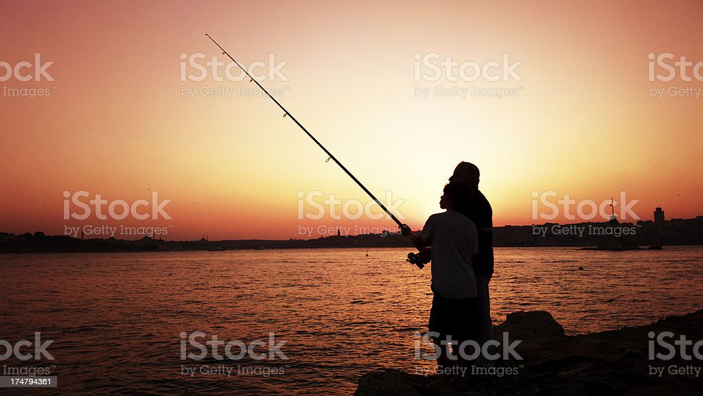 Little Boy And His Grandfather Fishing At Sunset royalty-free stock photo