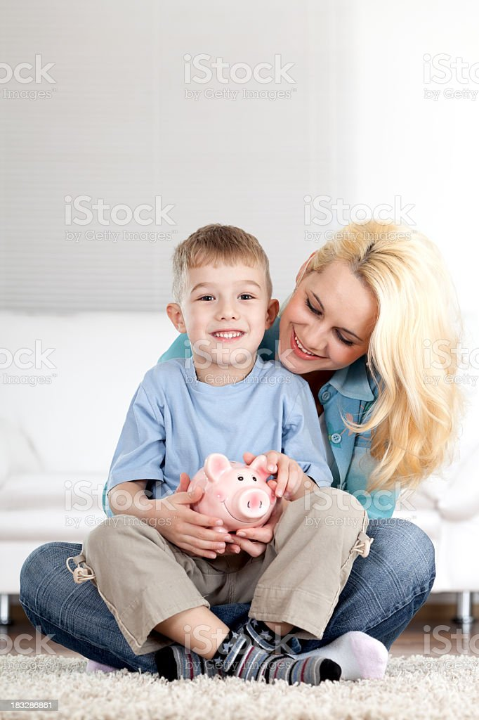 Little boy and his mother holding piggy bank, saving money royalty-free stock photo