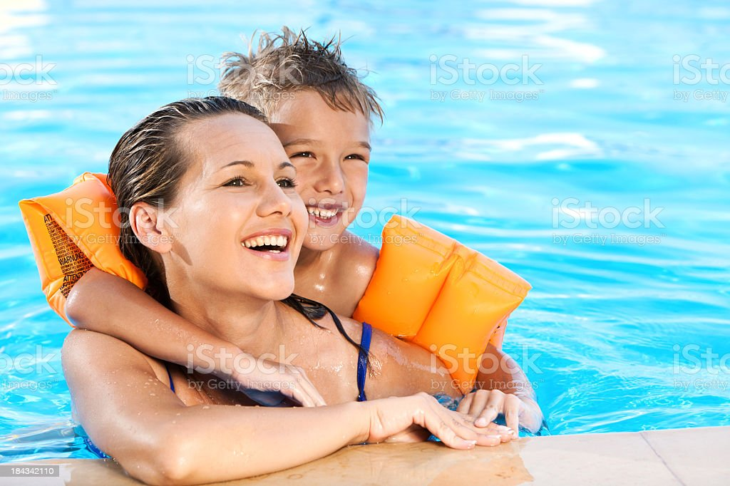 Little Boy And His Mother Relaxing In The Swimming Pool stock photo
