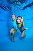 A little boy and his younger sister pose underwater in a children's pool. The boy smiles broadly, looks at the camera, and gives a thumbs-up. Closeup. Digital photo