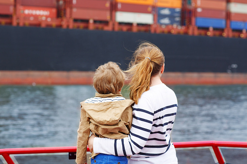 Little boy and mother watching ships on a ferry.