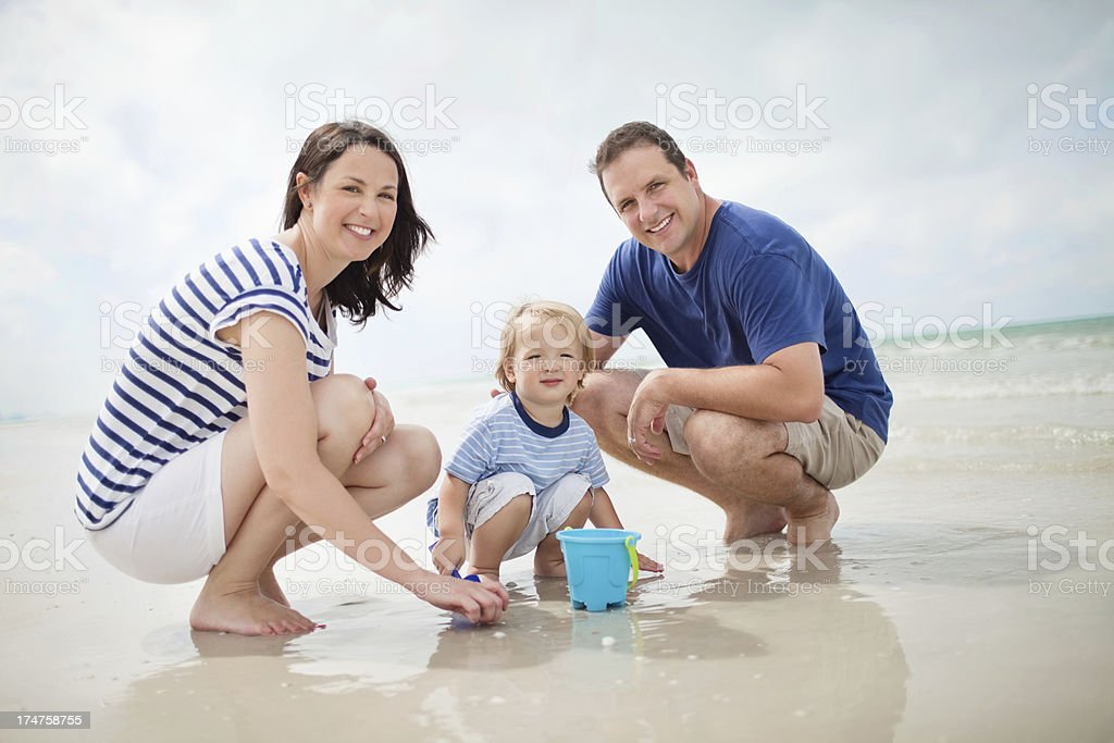 Little Boy And Parents Playing In Sand At Beach royalty-free stock photo