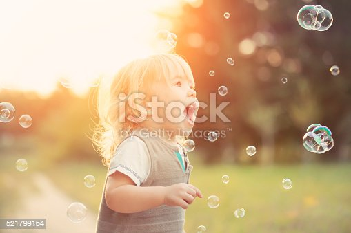 Little blonde boy playing with soap bubbles in a park.