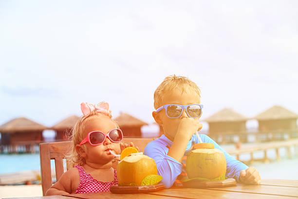 kleine jungen und mädchen trinken kokosnuss cocktail am strand - sonnenbrille kleinkind stock-fotos und bilder