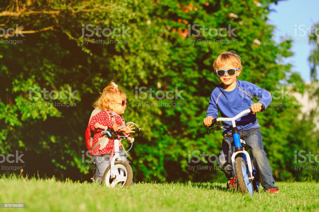 little boy and toddler girl on bikes in nature stock photo
