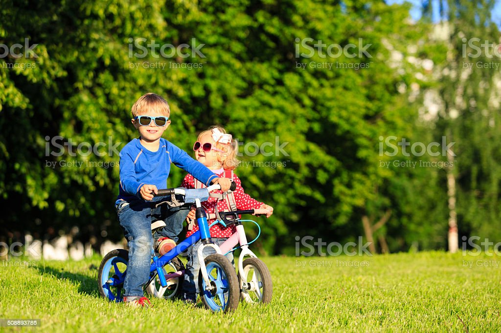little boy and toddler girl on bikes in summer park stock photo