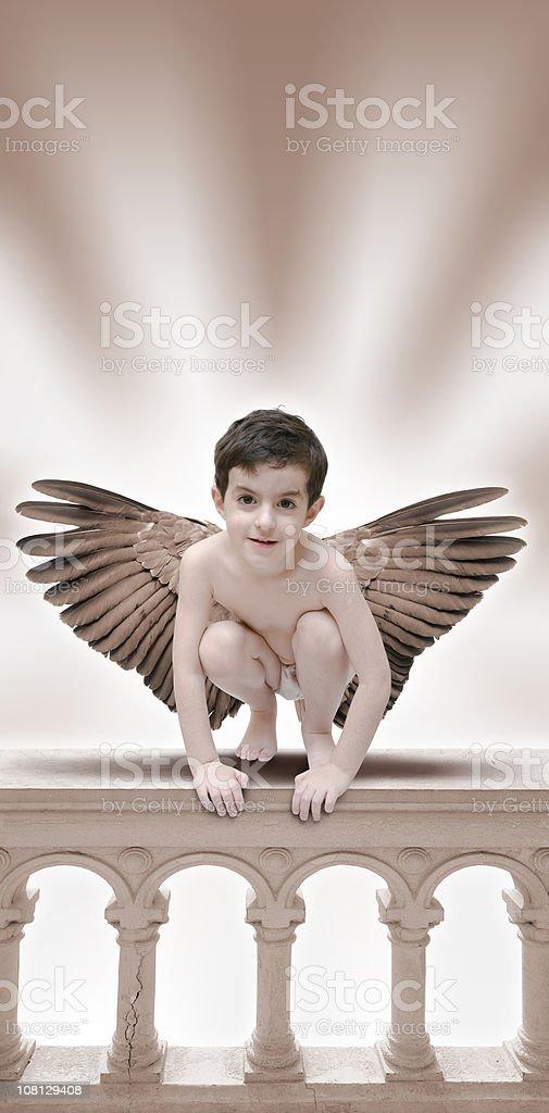 Little Boy Angel sitting on balustrade royalty-free stock photo