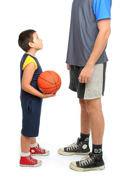 Little boy asking tall man to play basketball on white stock photo