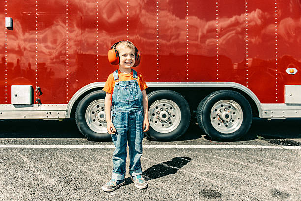 Little boy at a Car Race Little boy wearing earmuffs at a Car Race Pit Stop bib overalls boy stock pictures, royalty-free photos & images