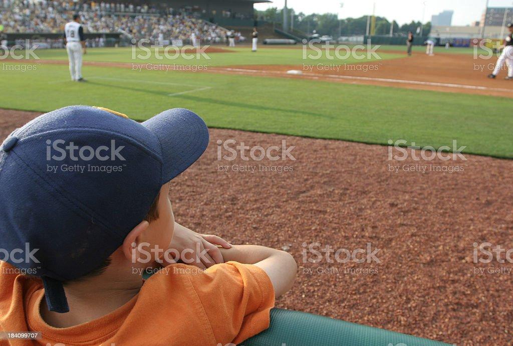 Little boy at baseball game dreams concept stock photo