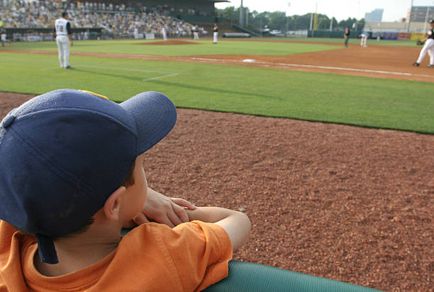 Little boy at baseball game dreams concept stock photo