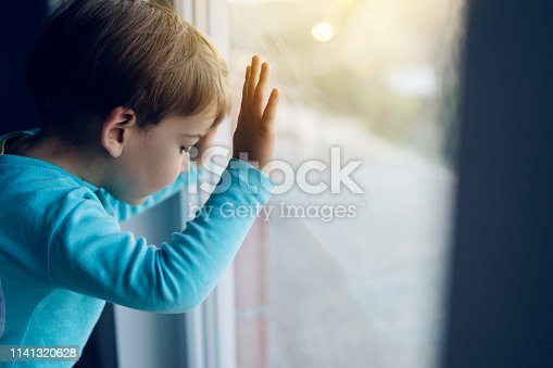 Little boy at home looking trough the window waiting for his mother to come back home