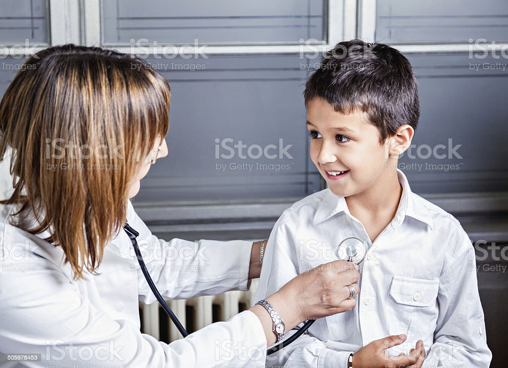 Little Boy At Pediatrician Little Boy and Female Pediatrician Doctor At The Doctor's Office On Medical Exam. 55-59 Years Stock Photo